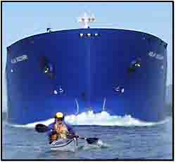 Dave paddling in front of an oil tanker.
